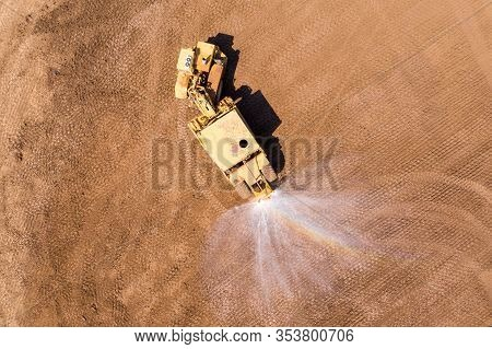 Articulated Water Truck Spraying Water, Aerial Image.
