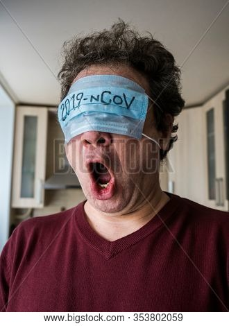 Shocked scared man with a medical mask on his face. Coronavirus panic concept