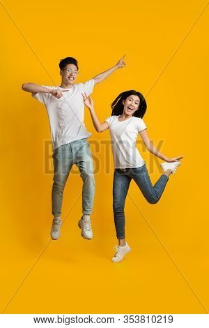 Breezy Asian Man And Woman Jumping In The Air, Having Fun On Yellow Studio Background
