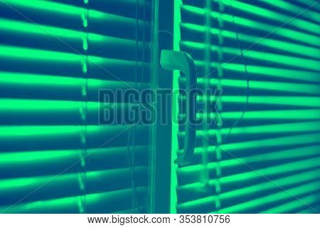 Closed Horizontal Blinds With Rope And Handle. Green Toned.