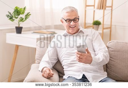 People And Technology Concept. Glad Mature Man In Specs Using Smartphone Sitting On Sofa At Home, Em