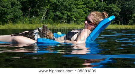 Pretty Young Woman on A Floating Chair On A Lake Smiling at a Shetland Sheepdog on Her Lap