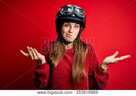 Young beautiful redhead motocyclist woman wearing moto helmet over red background clueless and confused expression with arms and hands raised. Doubt concept.