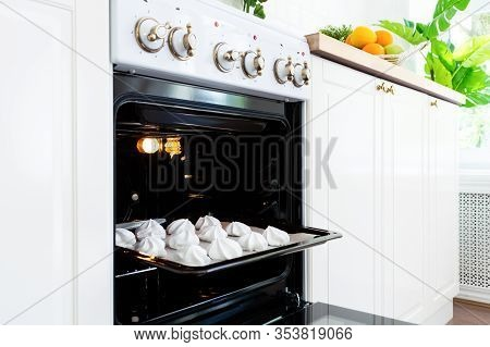 Baking Tray With Sweet Meringues In The Oven On Kitchen.