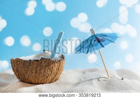 Tropical Beach Or Travel Concept: Summer Coctail In Coconut And Sun Umbrella.
