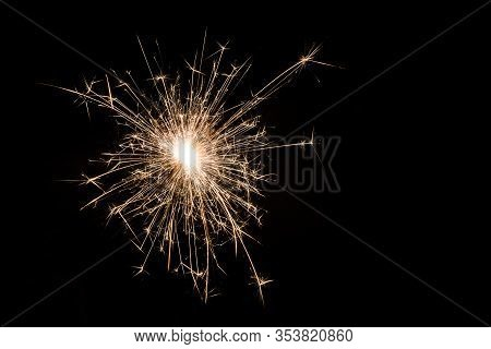 One Small New Year Sparkler On Black Background.