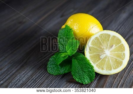 Fresh Lemons And Mint Leaves On A Dark Wooden Background.
