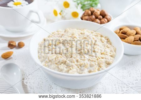 Oatmeal With Nuts In Bowl On White Wooden Table.