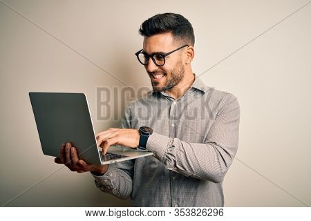 Young business man wearing glasses working using computer laptop with a happy face standing and smiling with a confident smile showing teeth