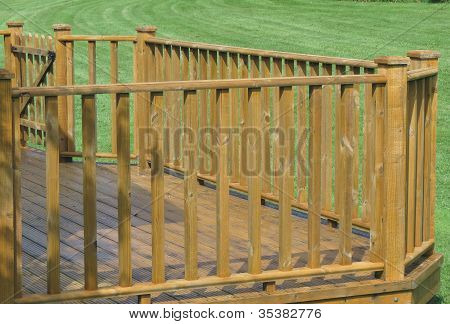 Wooden decking with ballustrade and gate in garden poster