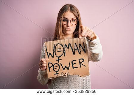 Young beautiful redhead woman asking for women rights holding banner over pink background pointing with finger to the camera and to you, hand sign, positive and confident gesture from the front