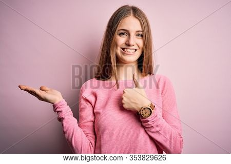 Young beautiful redhead woman wearing casual sweater over isolated pink background Showing palm hand and doing ok gesture with thumbs up, smiling happy and cheerful
