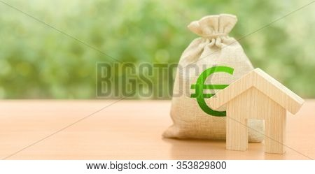 Wooden House Figurine And Green Euro Bag. Home Budget, Maintenance And Utility. Energy Efficiency. M