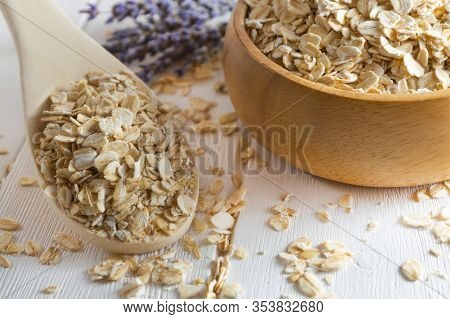 Organic Oat Flakes In Wooden Bowl And Spoon.