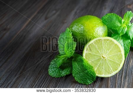 Fresh Lymes And Mint Leaves On A Dark Wooden Background.