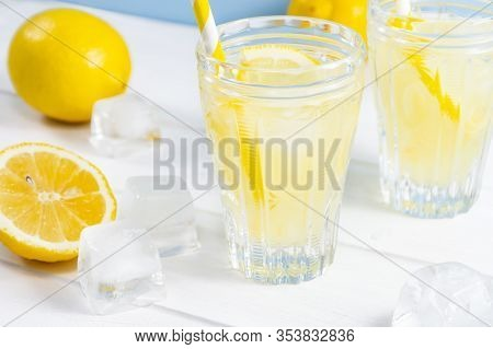 Glasses With Summer Drink Lemonade, Lemon Fruit And Ice Cubes On White Wooden Table.