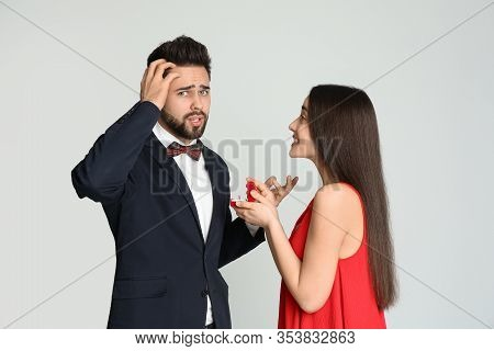 Young Woman With Engagement Ring Making Marriage Proposal To Her Boyfriend On Light Grey Background