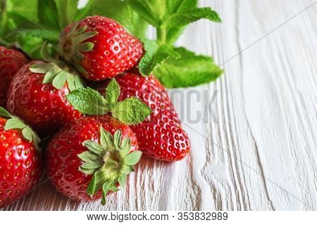 Fresh Strawberries And Mint Leaves On White Wooden Background.