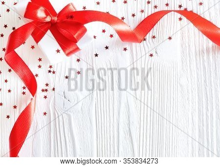 Gift Or Present Box With Red Ribbon And Stars Confetti On White Wooden Background. Holiday Concept,