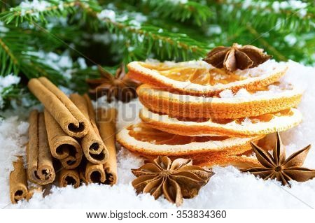 Christmas Spices - Cinnamon Sticks, Star Anise And Dried Oranges On The Snow Under Christmas Tree.