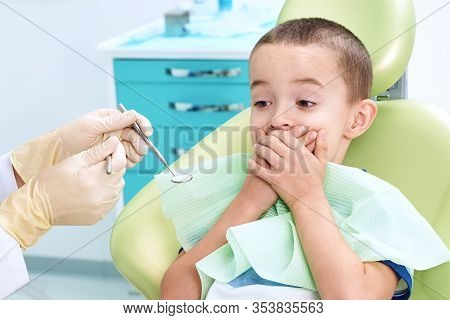 Portrait Of A Scared Child In A Dental Chair. The Boy Covers His Mouth With His Hands, Afraid Of Bei