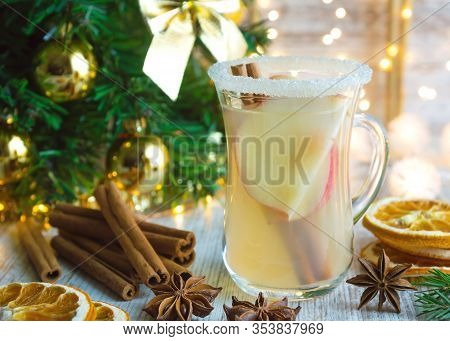 Christmas Hot White Mulled Wine In Glass With Apples, Cinnamon Sticks And Star Anise On Wooden Backg