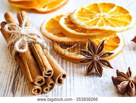 Christmas Spices - Cinnamon Sticks, Star Anise, And Slices Of Dried Orange On Old Wooden Background.