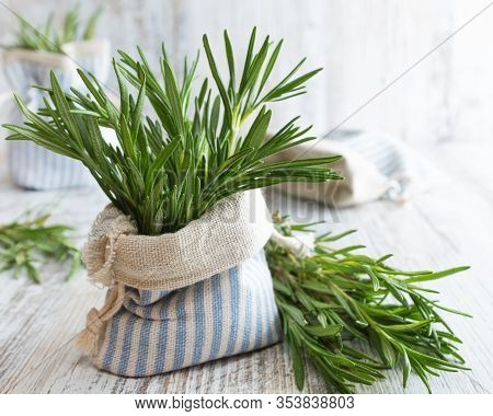 Fresh Green Rosemary In Decorative Linen Bag On An Old Wooden Table.