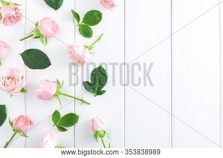 Spring Pink Flowers And Green Leaves On White Wooden Background. Flat Lay, Top View, Copy Space.