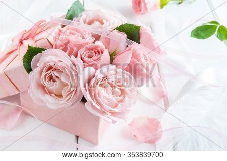 Beautiful Pink Flowers In Gift Box With Ribbons Closeup On White Wooden Table.