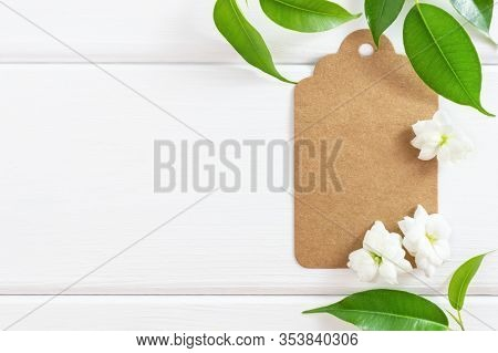 Spring Or Summer Mockup With Postcard, Green Leaves And Flowers On White Wooden Background. Flat Lay