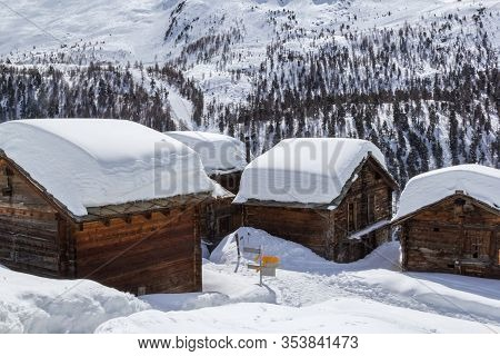 Village Eggen In Winter With Deep Snow Covered Roofs In The Swiss Apls, Zermatt, Switzerland