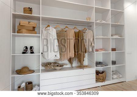 Side View On Minimalistic Modern Scandinavian White Wood Walk In Closet With Wardrobe In Neutral Bei