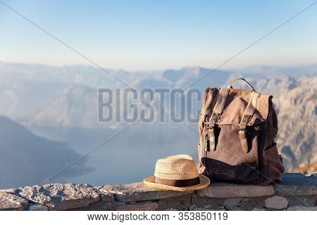 Travel Backpack And Straw Hat In Mountains. Traveler Bag On Stones. Concept Of Enjoying Traveling, V