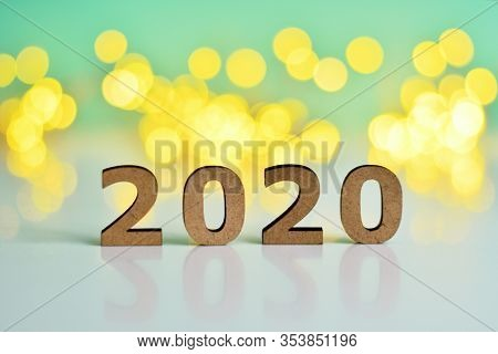 Wooden Numbers 2020 On A Green Background With Bokeh New Year's Lights.the Concept Of The New Year,