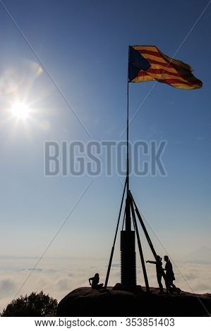 Backlight Of People With Mast With Catalonia Flag On A Mountain