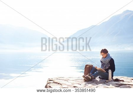 Young Woman Reading Book At Sea Beach. Cozy Winter Picnic By Morning Mountains. Girl In Blue Scarf E