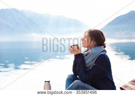 Young Woman Drinking Coffee At Sea Beach. Cozy Winter Picnic By Morning Mountains. Girl In Blue Swea
