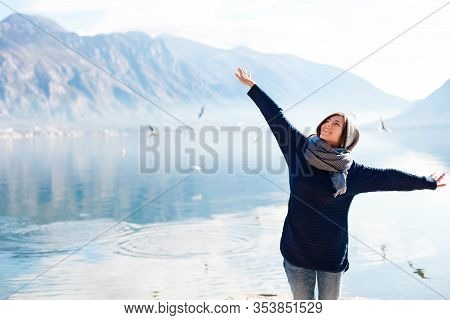 Happy Young Woman Like Flying Seagulls At Winter Sea Beach. Girl Traveler Smiling At Amazing Coastli
