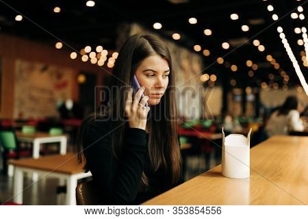 Lifestyle portrait of Real Young pretty woman with long hair on the phone
