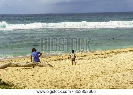 Mauritius Island, December 2019 - A Local Little Boy Walking On The Beach To The Sea Under The Watch