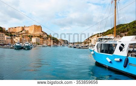 BONIFACIO, FRANCE - SEPTEMBER 19, 2018: A tourist takes pictures in the port of Bonifacio, in Corsica, France, with the famous citadel of the city in the background, on the top of a promontory