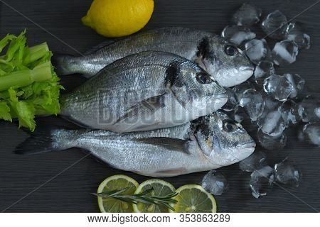 Raw Fish Dorado. Three Raw Fish Fillet On Iceand Lemon On Dark Background.healthy Food Concept. Medi