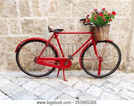 Red Bicycle With Flower Basket Againstold Stone Wall On Italian City Street.
