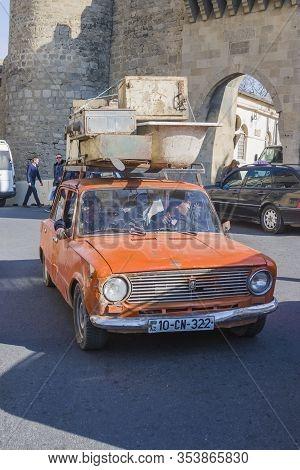 Azerbaijan, Baku-april 10, 2018; An Old Rusty Car Of The Fiat Lada Model Carries Old Scrap Metal On