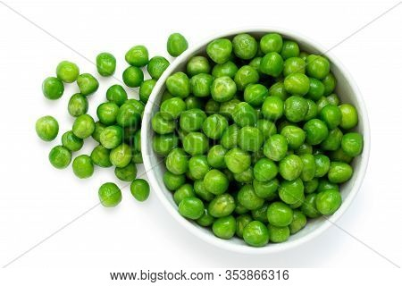 Fresh Green Garden Peas In A White Ceramic Bowl Isolated On White. Spilled Peas. Top View.