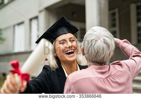 Graduate student in black gown wearing mortar board and holding degree running to embrace mother in campus. Portrait of excited young woman hugging her mom at graduation ceremony in university.