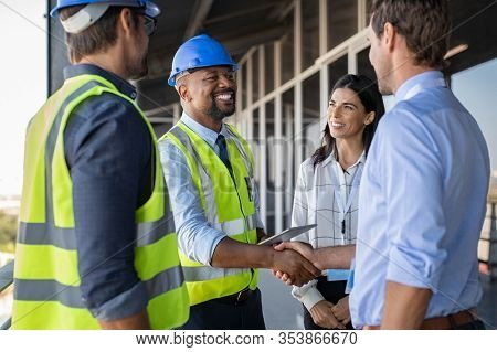 Smiling engineer shaking hands at construction site with happy architect. Handshake between african construction manager with businessman at bulding site. Team of workers conclude an agreement.