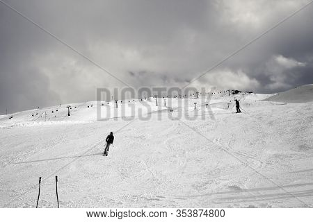 Snowy Ski Slope With Skiers In High Mountains And Cloudy Sunlit Sky At Winter Day. Ski Area Mottolin