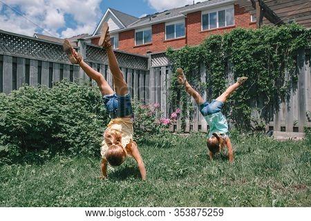Funny Sisters Girls Doing Cartwheel On Backyard. Excited Joyful Kids Playing Outdoor. Happy Lifestyl